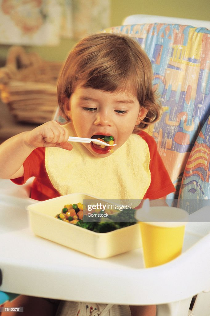 Young child sitting in highchair and eating vegetables : Stockfoto