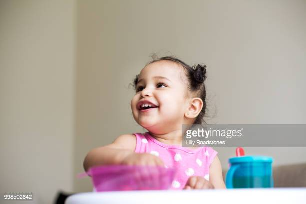 Young child smiling while eating from bowl
