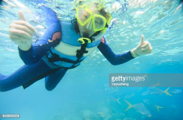 Young child  snorkeling in the tropical sea
