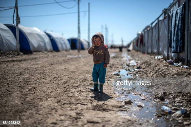 A young child stands alone looking towards the camera in Hamam alAlil refugee camp where large numbers of people have settled after being displaced...