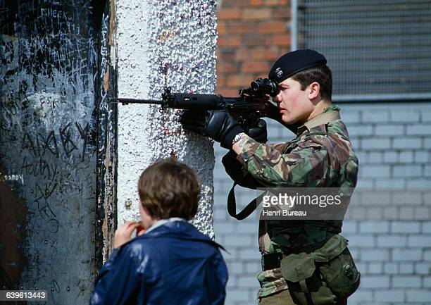 A young child stands near a British soldier in Belfast Northern Ireland