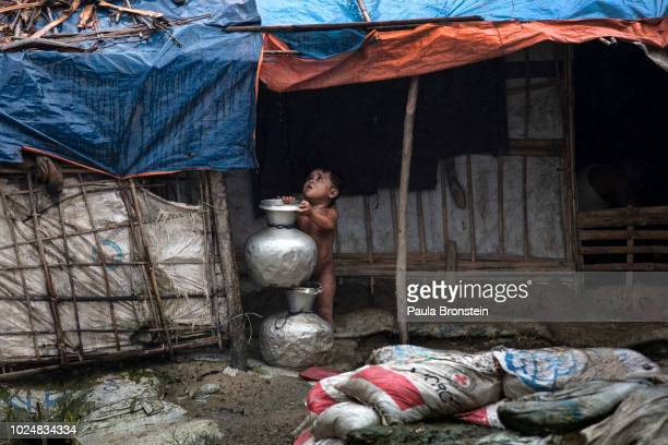 A young child stands under a shelter as monsoon rains hit the refugee camps August 28 2018 in Unchiprang refugee camp Cox's Bazar Bangladesh UN...