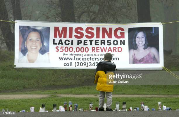 A young child stops to look at a makeshift memorial and a missing person's banner offering a halfmillion dollar reward for the safe return of Laci...