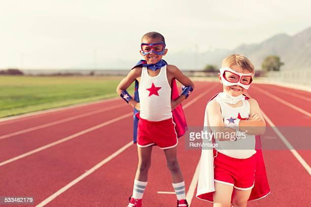 Jeune enfant Super-héros équipe se dresse sur piste