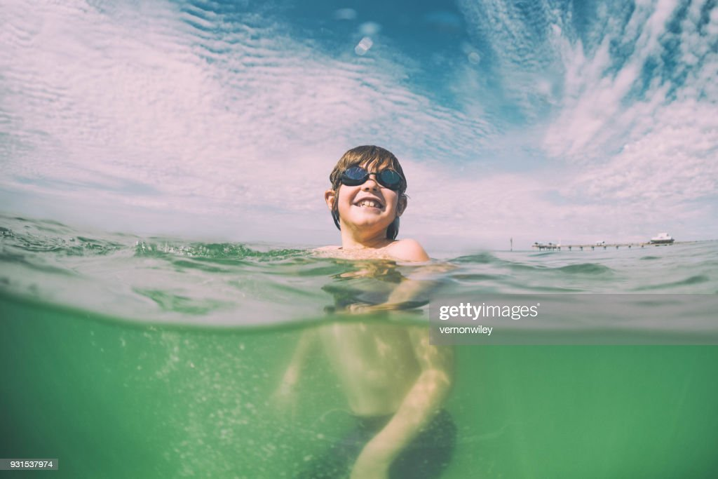 Young child swims in beautiful green waters of Florida : Stock Photo