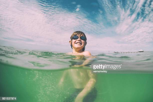 Young child swims in beautiful green waters of Florida