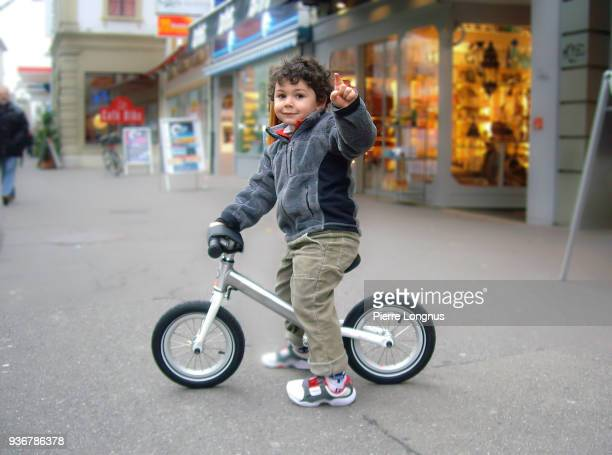 young child, three years old, showing off his balance bike
