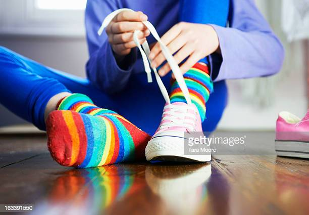 young child tying shoe laces with colourful socks - schoen stockfoto's en -beelden