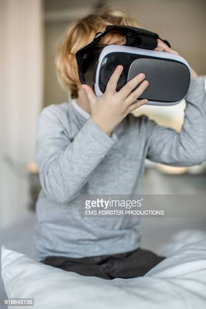 young child using a virtual reality headset in bed