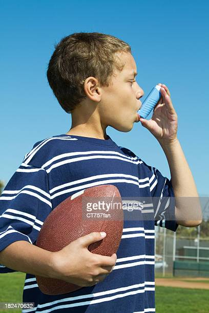 Young child using asthma inhaler, while holding football