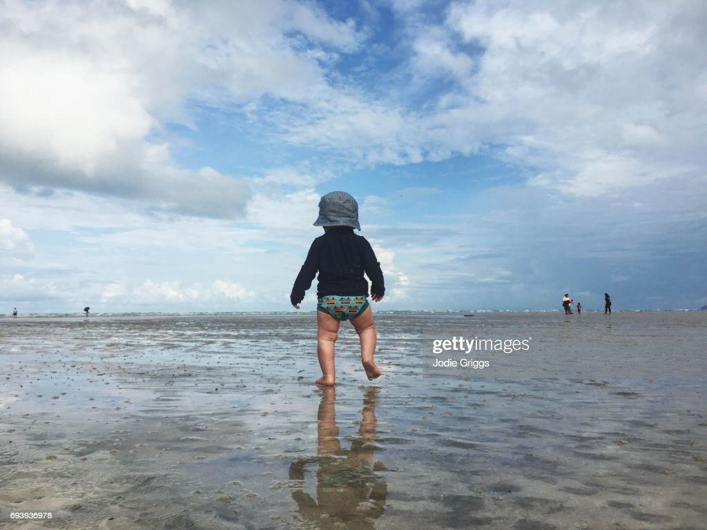 Young child walking alone on sand at the beach : Stock Photo