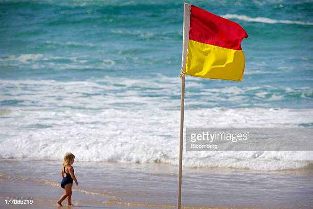 A young child walks towards the ocean past a safety flag on Main Beach on the Gold Coast Australia on Saturday Aug 17 2013 The Reserve Bank of...