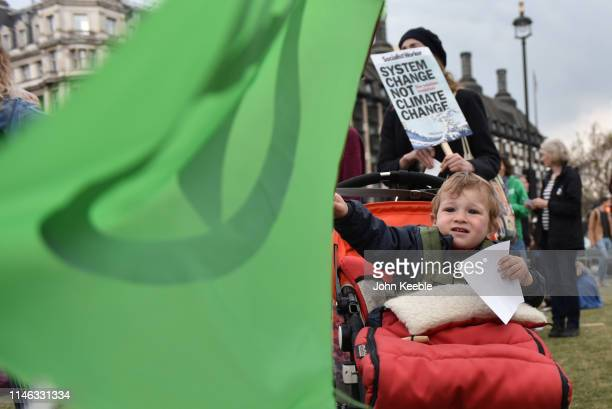 Young child waves an Extinction rebellion flag during a Climate emergency protest in Parliament Square outside the Houses of Parliament on May 01,...