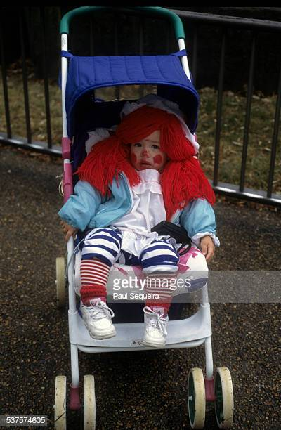 A young child wearing a Raggedy Ann costume sits in a stroller during Halloween events while visiting the Lincoln Park Zoo Chicago Illinois 1980s