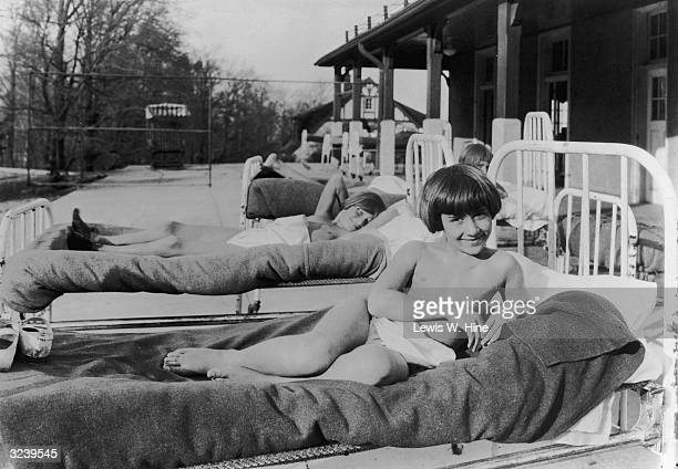 A young child wearing only underwear briefs reclines on a hospital bed outside a building during a sun treatment session possibly for tuberculosis...