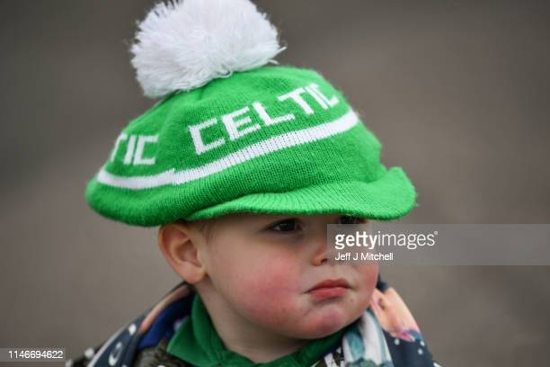 A young child wears a Celtic hat as hundreds of supporters gather at Celtic Park to pay their respects and watch the funeral of former Celtic player...