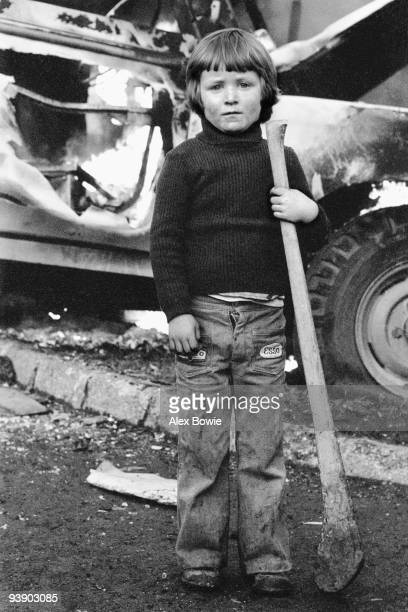 A young child with a hurley stick stands in front of a burning vehicle after hijacked vehicles were set on fire to celebrate the shooting of a...