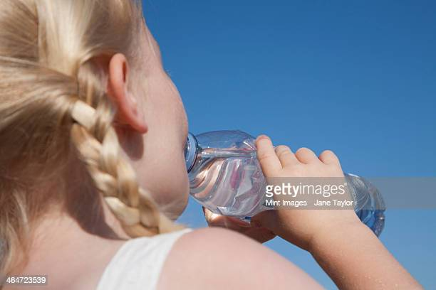 A young child with blonde hair in pigtails,drinking water from a clear bottle.