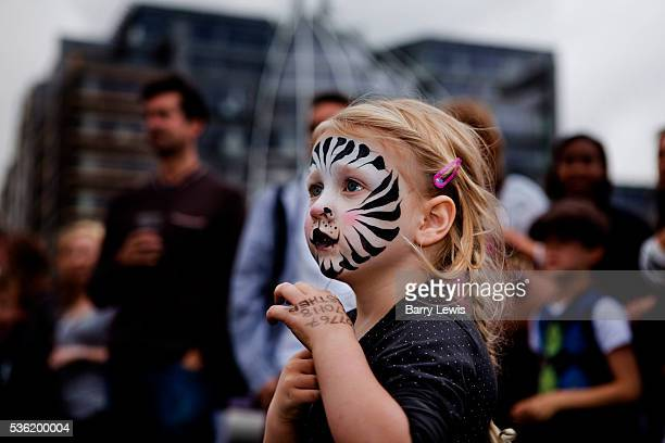 Young child with face painted as a zebra dancing on the bridge to Severed Limb a contemporary Londonbased skiffle band on Southwark Bridge which is...