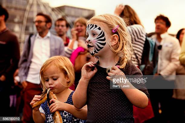 """Young child with face painted as a zebra dancing on the bridge to """"Severed Limb"""", a contemporary London-based skiffle band on Southwark Bridge which..."""