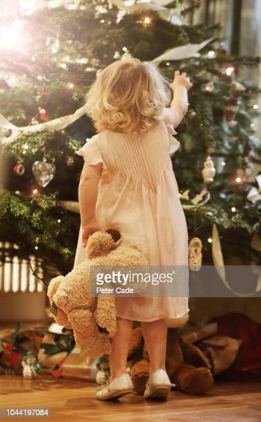 young child with teddy looking up at christmas tree -  キリスト教 伝来の地  ストックフォトと画像