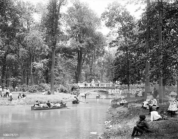 Young children and adults enjoy the quiet of Belle Isle Park in Detroit MI 1903 Boaters are visible on the pond while other park goers stand on a...