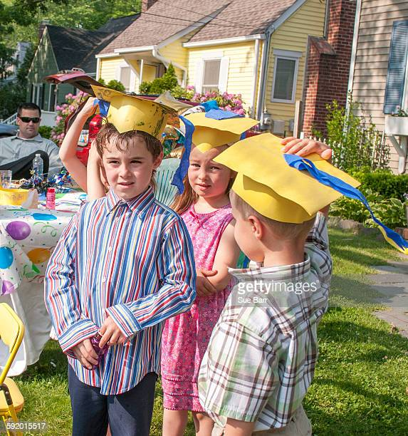 Young children at kindergarten graduation, wearing paper mortar boards