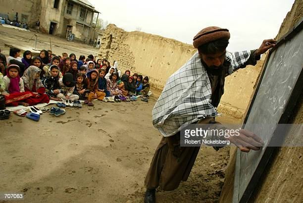 Young children at the Amir Dost Mohammad Khan school in Kabul, Afghanistan watch March 23, 2002 as their teacher writes out an exercise on the first...