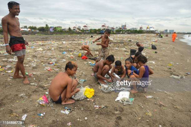 Young children clean different kind of shellfish they collected on the beach in Manila Bay near Baseco Compound The Batangas Shipping and Engineering...