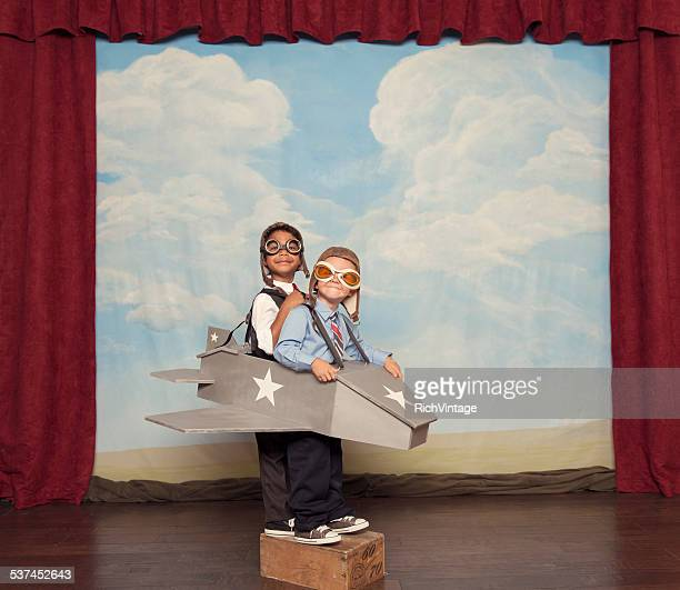 Young Children Dressed as Busnissmen in Toy Airplane