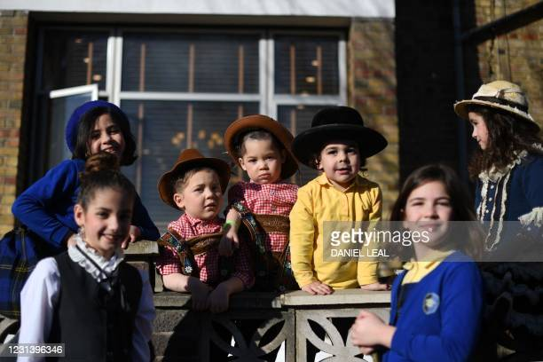 Young children dressed in costume in celebration of the Jewish holiday of Purim, pose for a photograph outside a house in the Orthodox Jewish...