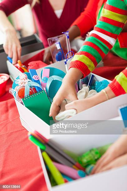Young children filling Christmas donation boxes for children in need