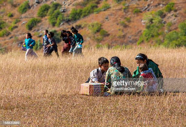 Young children have a picnic in the beautiful landscape around the village Chimi Lhakhang in the Punakha Valley with its temple monastery is renowned...