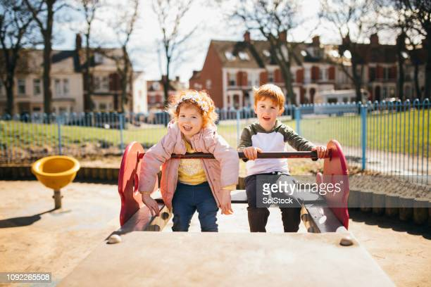 young children having fun in the park - britain playgrounds stock pictures, royalty-free photos & images