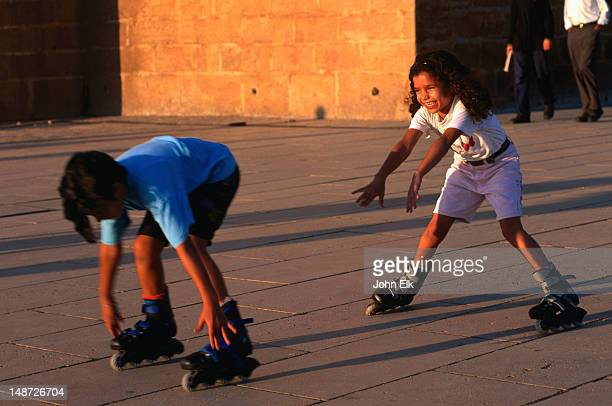 Young children having fun rollerblading.