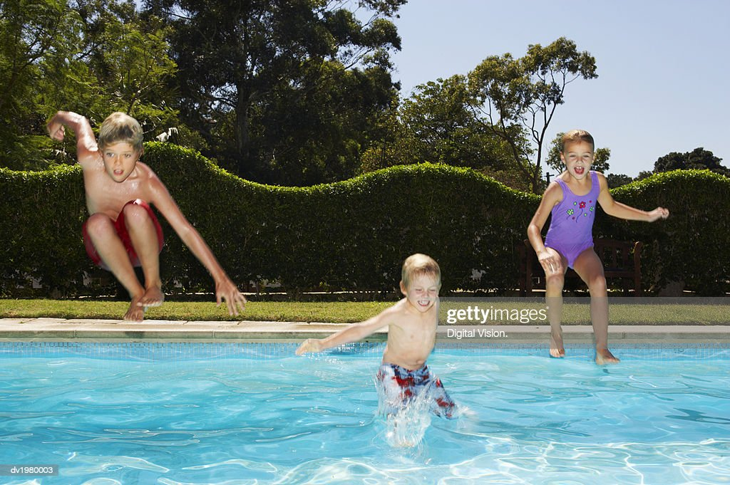 Young Children Jumping into a Swimming Pool : Stock Photo