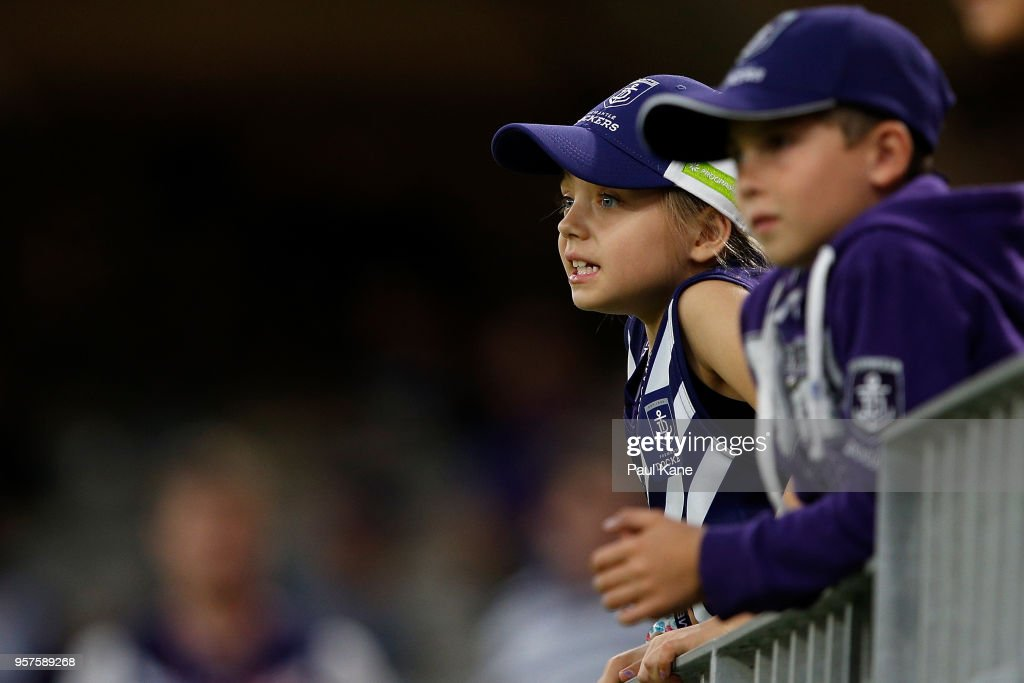 Young children look on as players warm up during the round eight AFL match between the Fremantle Dockers and the St Kilda Saints at Optus Stadium on May 12, 2018 in Perth, Australia.