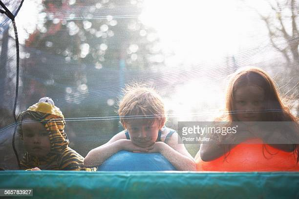 Young children looking out from garden trampoline