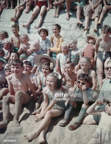 Young children on holiday sit on the sand to watch a puppet show on the beach at the seaside resort of Bournemouth in Dorset England in August 1952