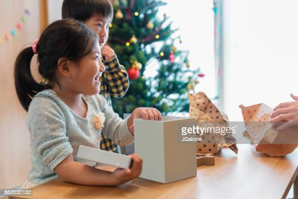Young children opening their Christmas presents