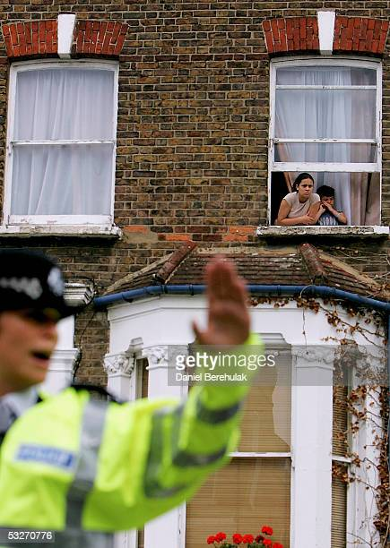 Young children peer from a window as a Police woman pushes the cordon back in front of a house under investigation on Portnall Road on July 22, 2005...