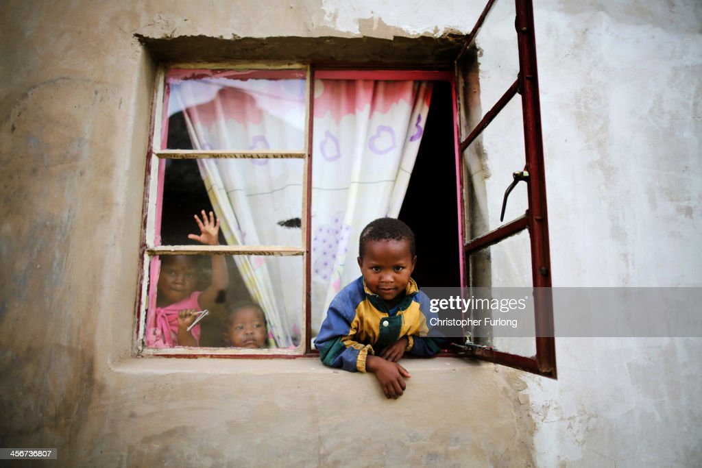 Young children peer from the window to watch the funeral of former South African President Nelson Mandela in his home village of Qunu on December 15, 2013 in Qunu, South Africa. Mr. Mandela passed away on the evening of December 5, 2013 at his home in Houghton at the age of 95. Mandela became South Africa's first black president in 1994 after spending 27 years in jail for his activism against apartheid in a racially-divided South Africa.