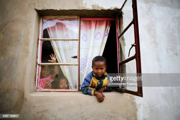 Young children peer from the window to watch the funeral of former South African President Nelson Mandela in his home village of Qunu on December 15...