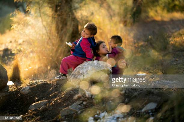 Young children play in the olive grove in the unofficial camp outside the Moria Refugee Camp on October 14 2019 in Mytilene Greece Moria migrant camp...