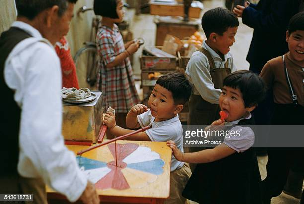 Young children playing a game to win candy Naha Okinawa Prefecture Japan circa 1965