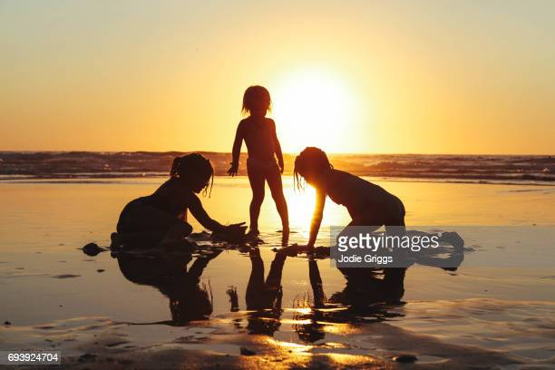 Young children playing happily together at the beach during sunset