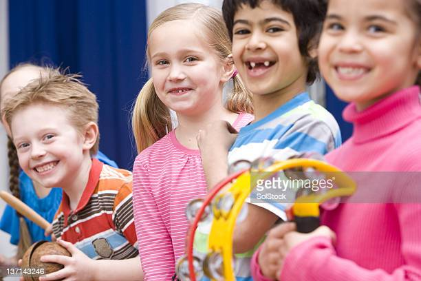 young children playing instruments in their music class - percussion instrument stock photos and pictures