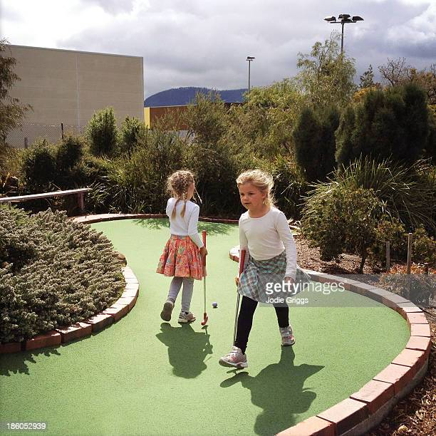 Young children playing mini golf outside