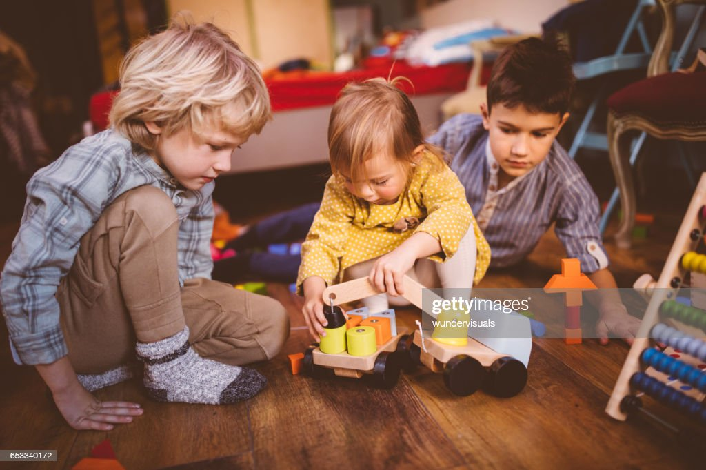 Young children playing with toys on bedroom floor : Stock Photo