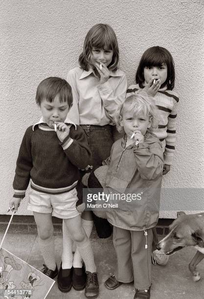 Young children puff on fake cigarettes in Salford Greater Manchester circa 1980